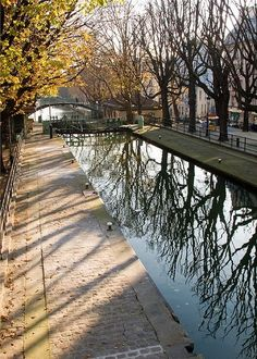 Canal Saint-Martin, Paris, with tree reflections in water & shadows on sidewalk.