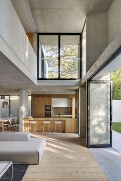 Kitchen, dining area, and living room in natural colors, wood, and concrete by Nobbs Radford Architects