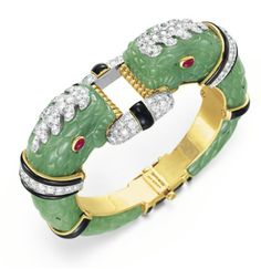 A JADE, DIAMOND, RUBY AND ENAMEL BANGLE BRACELET, BY DAVID WEBB  Designed as two opposing carved jade chimera heads with cabochon ruby eyes, enhanced by circular-cut diamond and black enamel detail, joined by a circular-cut diamond and black enamel open link, mounted in 18k gold and platinum