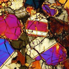 This is a photograph of the NWA 998 Martian meteorite. This is a photo of a thin section of this meteorite viewed through a microscope using transmitted cross polarized light. The different colors indicate the mineral and crystal composition of this meteorite.