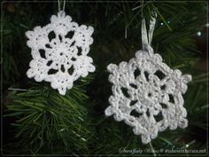 two crochet snowflakes hanging in a christmas tree - www.wishesintherain.net
