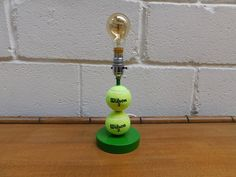 SMALL TENNIS BALL LAMP Custom made green based table lamp with 2 tennis balls. Rewired with new bulb holder, cable and 3 amp plug. PAT tested with label to base. Lovely fun item for the tennis lover Balls, Tennis, Label, Table Lamp, Green, Fun, Table Lamps, Lamp Table, Hilarious