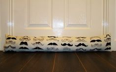 Home comforts - you wouldn't find one of these in Fawlty Towers!   Handmade Moustache Draught Excluder, via Etsy.