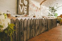 """Picket Fence-esque Table - this is the head table at a rustic wedding but can see this concept for a sweet table at a birthday party or any outdoor party. Love the """"love"""" sign in the background too."""