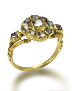 A gold and diamond ring, probably Portuguese, 17th century and later  The central circular cluster, probably 17th century, composed of table-cut diamonds within an engraved closed-back setting, to later table-cut diamond scroll shoulders and hoop, probably 18th century, the whole mounted in yellow gold