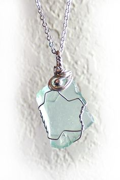 The aqua sea glass in this handmade pendant is perfectly smooth, though still fairly angular. It's set in a sterling silver wire wrap that has angles and gentle swoops and a sterling accent bead. $48