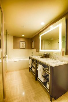 These Impressive D.C. Hotel Penthouse bathrooms has woven tile flooring, dark vanities, open shelving, marble countertops, a backlit mirror, dual sinks, mirrored walls, and built-in bathtubs.