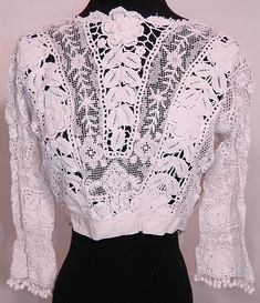 Edwardian Antique White Irish Crochet Tape Lace Bodice Blouse. This Edwardian era antique white Irish crochet tape lace bodice blouse dates from 1910. It is made of a white sheer Irish crochet tape lace with connecting thread picot ornamented bars, crochet ball fringe trim, filet lace and embroidered net inserts.