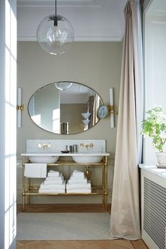 Modern glamorous bathroom at Stockholm's Ett Hem Hotel designed by Ilse Crawford with gold and glass accents