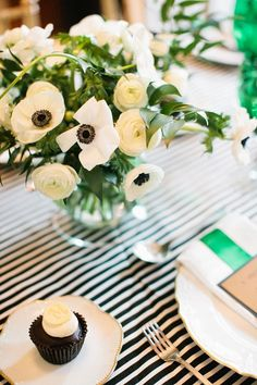 Color theme: black, white and green. White ranunculus and anemone center pieces, black and white striped tablecloth and cloth napkins, green goblets and ribbon (on the plate settings).