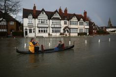 A couple promote the Piccola Venezia Italian restaurant by rowing their gondola through flood waters on February 12, 2014 in Datchet, England. (Peter Macdiarmid/Getty Images)