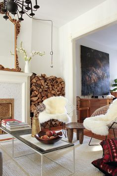 Mirrors, sheepskin throws, and gilt soften the hard angles and clean whites, with a pop of red to liven it up.