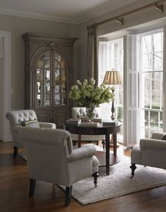 Shutters with draperies and four chairs -- all in neutral palette.