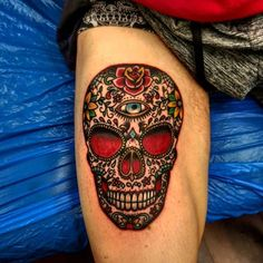 Very detailed sugar skull tattooo on mans thigh with a lot of small symbols