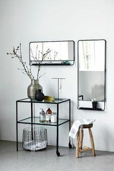 Une belle console d'entrée en fer noir et verre, bien combinée avec un miroir mural!