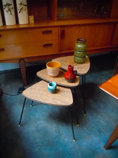 This is a cool 1950s set of three nesting tables with triangle shaped tabletops. The plywood tabletops have a light brown colour. The legs are made of black painted iron and can be detached. The little tables are in good condition!