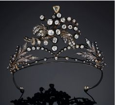 AN ASYMMETRICAL DIAMOND TIARA. Ofᅠopen workedᅠfoliate spray design,ᅠ setᅠ throughoutᅠwithᅠrubbedᅠcollet-setᅠ andᅠclaw-setᅠcushion-shaped,ᅠcircular cut and roseᅠdiamonds. (Sotheby's)