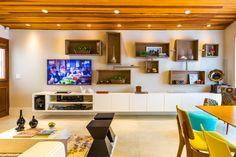 """A casa paulistana localizada no bairro do Brooklin, de 200 m² ganhou uma área social toda integrada: o estar e a cozinha são separados do quintal e da churrasqueira somente por uma porta de vidro. Arquiteta Juliana Yamakawa, do escritório BY Arq&Design, que assina o projeto junto com a designer de interiores Ananda Bello. """"Não queríamos utilizar painel de madeira na parede da TV e optamos por nichos com diversos tamanhos e interligados para dar movimento e marcar a parede"""""""