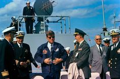During a visit on board the United States Naval ship USS Observation Island (EAG-154) at sea off the coast of Florida, President John F. Kennedy (center left, wearing sunglasses) puts on a windbreaker bearing the insignias of the USS Observation Island and the submarine USS Andrew Jackson (SSBN-619) presented as a gift from the crews of both ships. Photo: John F. Kennedy Presidential Library and Museum , DID # JFKWHP-ST-C400-38-63 — with Erik Reynolds, Thomas Walker and John F. Kennedy.