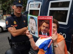 A woman holds portraits of Spain's Prime Minister Mariano Rajoy (L) and Spain's former Prime Minister Jose Luis Rodriguez Zapatero as she protests with around 300 people against corruption outside the PP (Popular Party)'s headquarters, in Madrid on July 9, 2013. AFP PHOTO/ DOMINIQUE FAGET