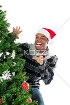 happy young man gesturing while standing beside chritsmas tree. - Happy young man gesturing while standing beside chritsmas tree against white background, Model: Eddie Reid