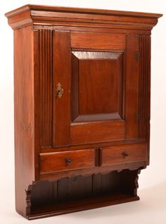 """PA Chippendale Walnut Hanging Cupboard. : Lot 720 Pennsylvania Chippendale Walnut Hanging Cupboard. Molded cornice, raised panel door, flanked by reeded stiles, two split lower lip molded dovetailed drawers, lower shelf with scalloped skirt and supports, dovetailed construction. 35-1/2""""h. x 26-3/4""""w. x 10- 1/2""""d. Condition: Very good, expected wear, old refinish. Harry Hartman Sold $3500"""