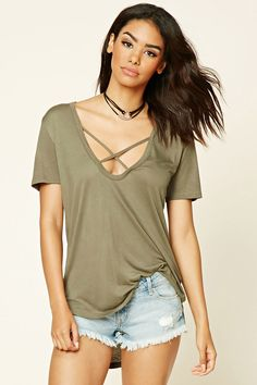 A knit top featuring a scoop neckline with crisscross straps, short sleeves, and a rounded high-low hem.