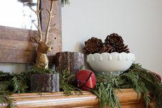Entry table: reindeer + pine cones + sleigh bells + milk glass