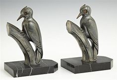 Pair of Art Deco Patinated Spelter Bookends, c. 1930, of woodpeckers with glass eyes, on striated black marble bases