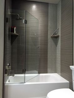 his has become a new addition to custom shower options for tubs. It folds to off full access to the tub without the hindrance of a standard slider shower door. It has no metal and is supported by the hinges with a sweep on the tub for smooth reclining when opened. It's profile is simple and elegant for any bathroom.