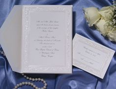 T5727  Delicate embossed flowers surround a beaded pearl border on this bright white invitation.