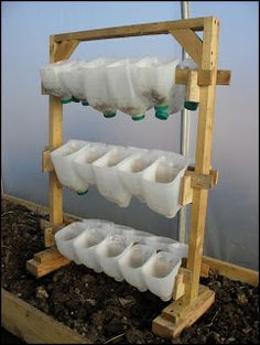 cut open milk jugs and string their handles through a piece of wood to make a vertical garden.  She leaves the lids on.  You could use a bit of fabric or burlap, tied over spout, so they could drain and if you line them up one over the next, they would drain down into the next one so you only have to water the top?