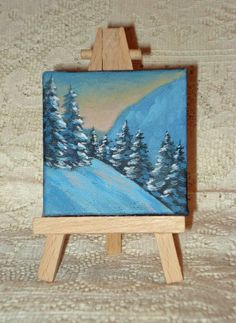 This painting is approximately 2 3/4 x 2 3/4 inches. It is painted with acrylic paint. The sides are painted a dark blue color. It comes with an easel. This painting is signed by the artist on the bottom edge of the canvas.: