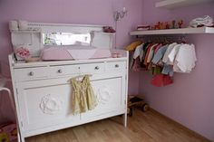 Old white dresser with a pink baby changing mat on top of it. A small white shelf with baby clothes hanging up