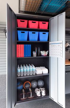 Open cabinet with baskets, binders, bottled water, towels and excercise balls.                                                                                                                                                                                 More