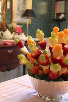 Adorable fruit arrangement (Edible Arrangement style). Thread fruit on to wooden skewers (the pineapple was cut into heart shapes with a cookie cutter).   Then stick the skewers into a grapefruit that was placed in a bowl and covered with kale.