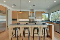 Noticing cabinets in the island with stools in front. Modern look with lighter cabinets which you don't see much.