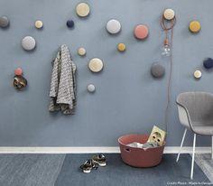 Plusieurs patères de couleurs différentes habillent un mur d'entrée peint en bleu. De tailles différentes, ils donnent un esprit fun et ludique à l'entrée !