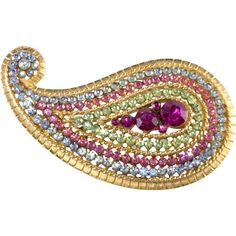 Paisley brooch comprised of rhinestones in pale blue, fuchsia and bright pink, and peridot green in a brushed gold plated setting. We believe this one