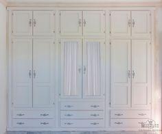 Armario empotrado a medida en color blanco con los filos desgastados. Puertas abatibles con altillo independiente y cajones por fuera. Dos puertas centrales con cristal para visillo.