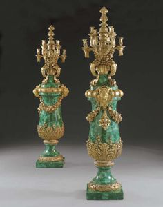 A massive pair of French ormolu-mounted malachite twelve-light torcheres  Late 19th Century, The malachite 20th Century  Surmounted by a knop finial and scrolled candlearms, supported by four grotesques, the baluster uprights with acanthus leaf collar and gadrooned shoulder and applied with masks and swags, on circular socles with laurel foot above a square base  90½ in. (230 cm.) high (2)