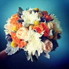 Vibrant bridal bouquet with commercial mums, garden roses, spray roses, eryngium, craspedia and dusty miller.
