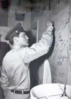 Elvis putting up a message in the men's toilets, I wonder what it says?