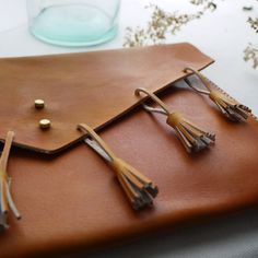 Hand crafted tan leather multi fringe clutch bag.   Colour