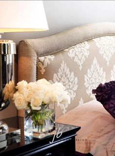A Pretty headboard using a patterned fabric with a solid fabric on the edge with nailhead trim inbetween