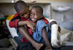 Jean-Pierre Kalikunshe (L), 10, comforts his friend Espoir Kangeshe, 6, both of whom have had surgery to correct leg deformities, at the Heal Africa hospital in Goma, February 10, 2009. Kalikunshe and Kangeshe are among some 70 children looked after by Stand Proud, a charity that assists children suffering from polio and other leg defects in war-ravaged Democratic Republic of Congo, where 15 years of war has devastated public health services.