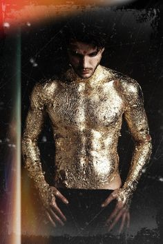 gold flaking paint -- or any color really, gives a cool mystical effect to a person (and adding extra shine/shadow for muscle definition is probably less noticeable)