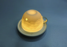 The Lighting Cup designed by Jin-woog Koo of the Nothing Design Group. The Lighting Cup is designed for everyday use. It is useable as a teacup and as a delicate lighting cover for the provided LED saucer. When illuminated, moonlit landscape is illustrated gently on the cup.