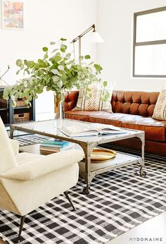 Living room with brown leather couch, patterned pillows, white walls, large plants, colorful artwork, silver coffee table, black and white checkered rug, white chair and brass floor lamp