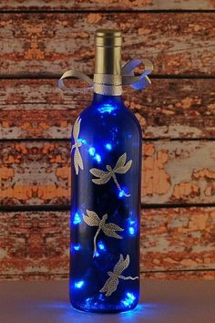 Blue and white dragonfly wine bottle lamp. An empty clear wine bottle was reclaimed and repurposed into this wine bottle light. After cleaning and removing the labels, the clear bottle was tinted a deep blue. Silver and white dragonflies were hand painted Liquor Bottle Crafts, Glass Bottle Crafts, Wine Bottle Art, Painted Wine Bottles, Lighted Wine Bottles, Bottle Lights, Diy With Glass Bottles, Decorating With Wine Bottles, Wine Bottle Lighting